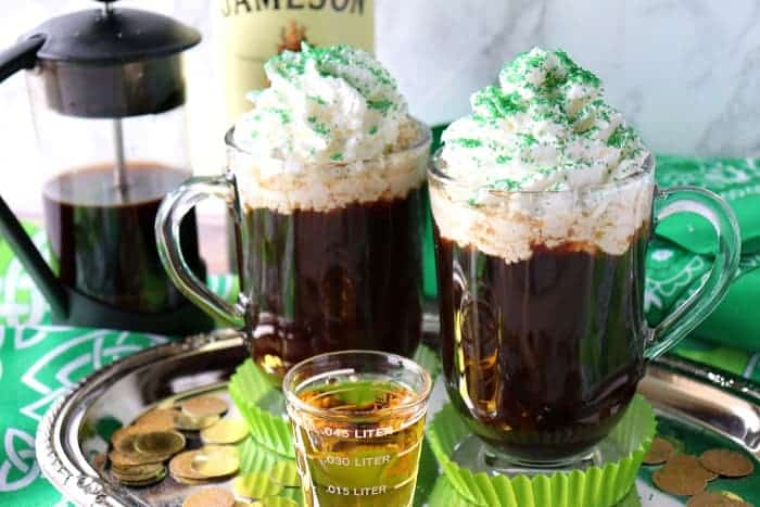 Two mugs of Irish Coffee with a shot of whiskey, whipped cream and green sugar.