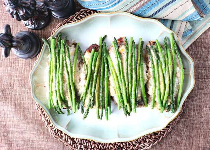 Overhead picture of a platter of chicken oscar with fresh asparagus spears