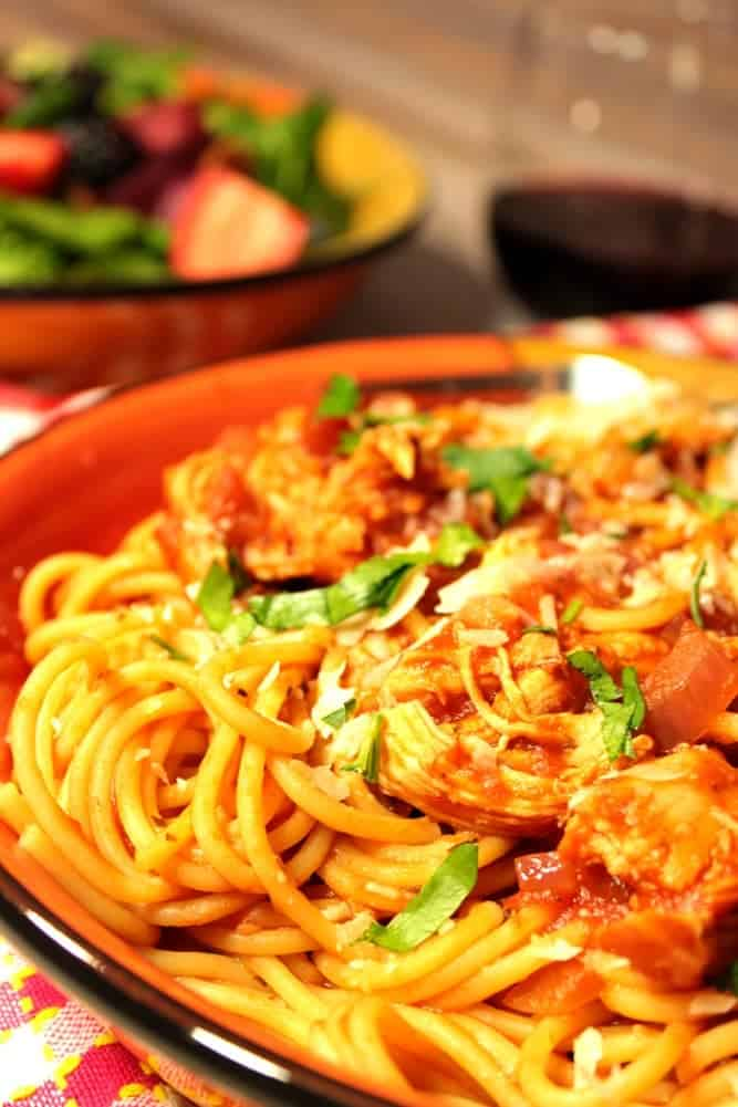 Closeup of a bowl of spaghetti with chicken, a salad and glass of wine in the background.