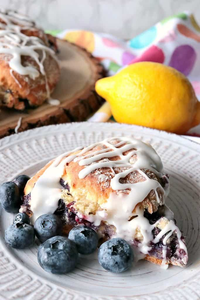 Scone on a white plate with fresh blueberries and a lemon in the background.