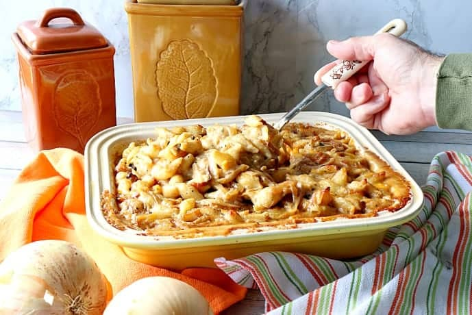 Hand with a spoon serving up French onion mac and cheese out of a casserole dish. Popular Thanksgiving side dish recipe roundup.