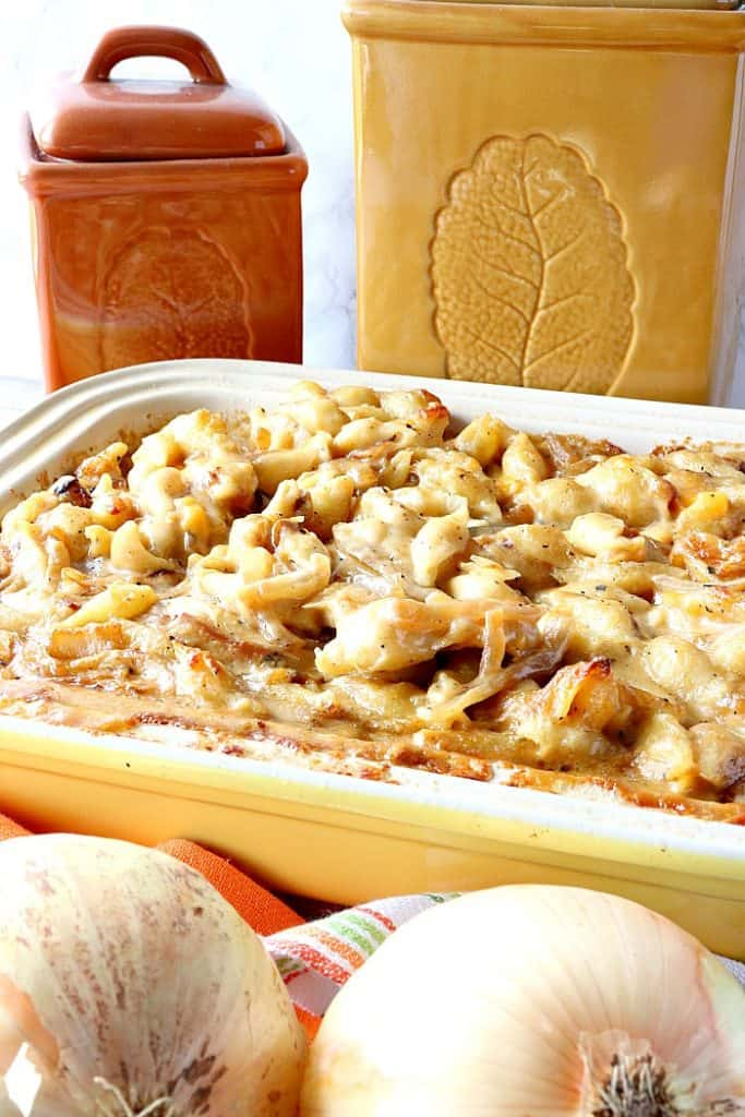 Vertical image of baked mac and cheese in a casserole dish with onions in the foreground and canisters in the background.