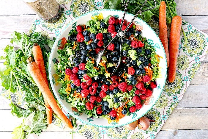 Overhead photo of a large bowl of colorful kale salad with carrots, kale, and shallots surrounding the bowl as accents.