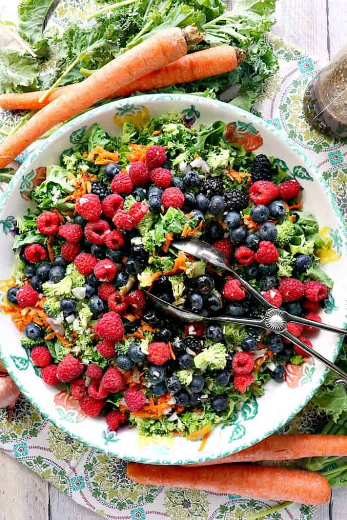 vertical image of kale berry salad with carrots, kale, broccoli, and a salad server.