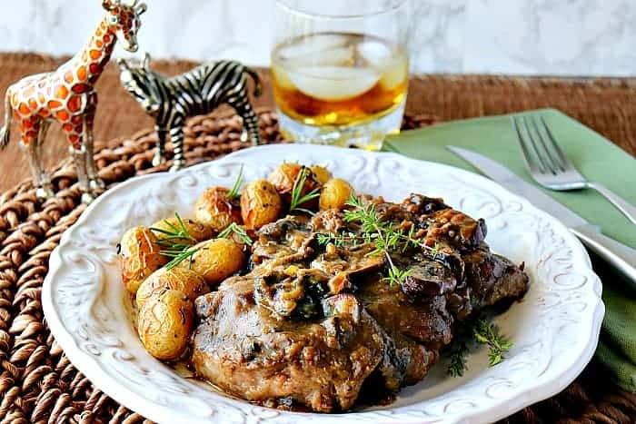 Steak with mushroom sauce on a white plate with baby potatoes and a glass of bourbon on the rocks in the background.