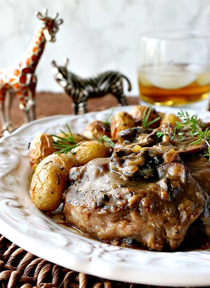 Closeup vertical image of a steak covered in mushroom sauce with a glass of bourbon and ice in the background.