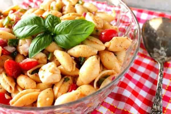 Glass bowl filled with Italian Shell Pasta Salad with fresh basil leaves and a red and white checked napkin underneath.