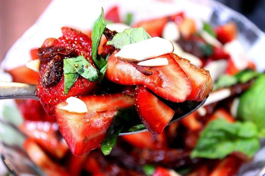 Closeup image of strawberry basil salad. Sun-dried tomatoes and slivered almonds are also included.