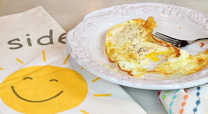 Smiling sunshine napkin and a white plate with air fryer fried eggs and a fork.