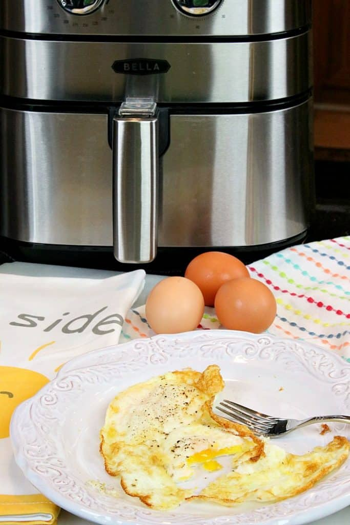 vertical photo of fried eggs on a white plate with an air fryer in the background