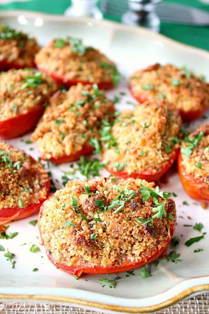 Closeup photo of a plate of Italian roasted plum tomatoes with breadcrumbs and Parmesan cheese.