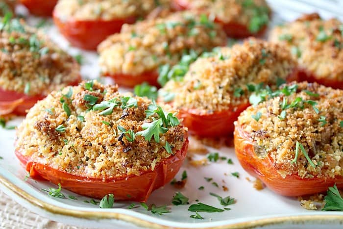 Side view of a plate of roasted plum tomatoes with parsley and breadcrumbs.