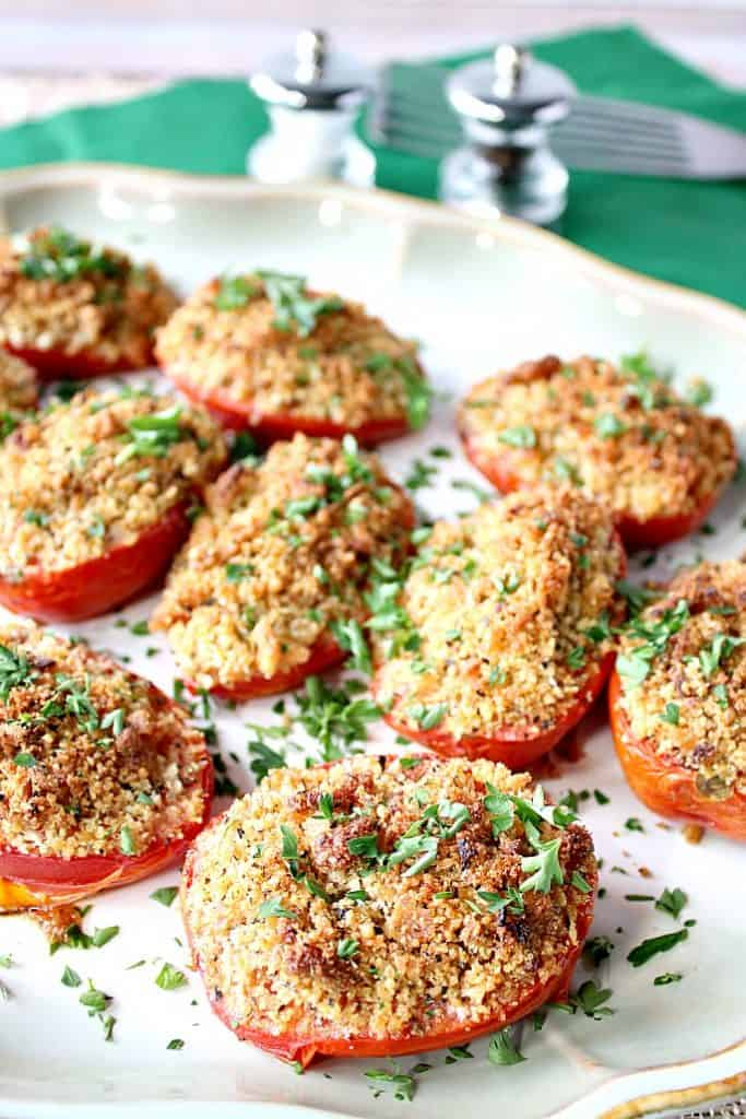 A plate of roasted tomatoes with breadcrumbs and Parmesan cheese topping with a salt and pepper shaker in the background.