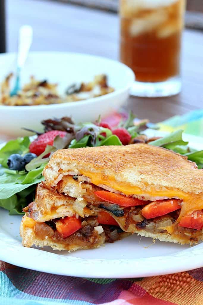 vertical photo of a grilled cheese sandwich with caramelized onions and red bell pepper on a white plate with a salad in the background.