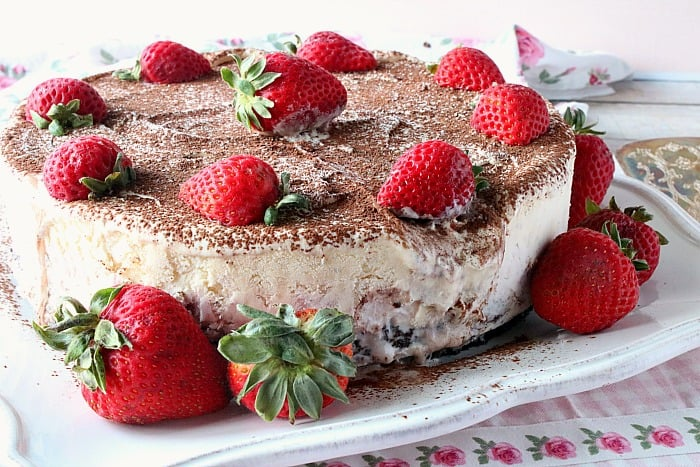 Melting Neapolitan ice cream cake with strawberries on a square white plate.