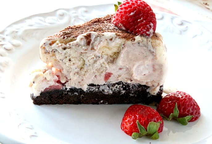 A single slice of Neapolitan ice cream cake on a white plate with a strawberry garnish.