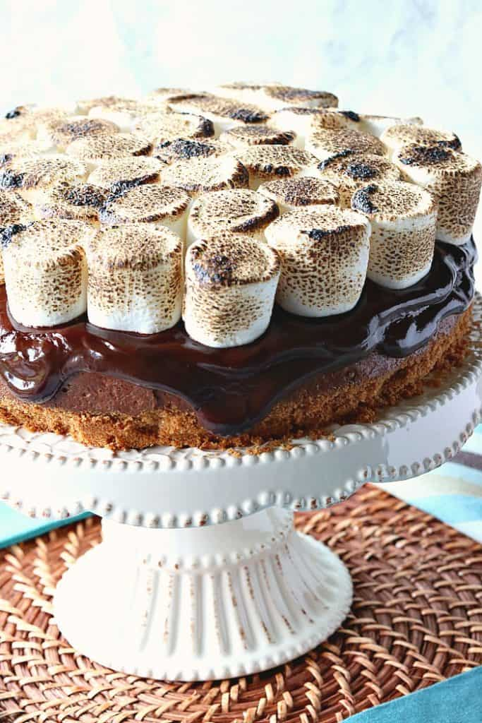 A closeup of a s'mores cheesecake with chocolate ganache and toasted marshmallows on top.