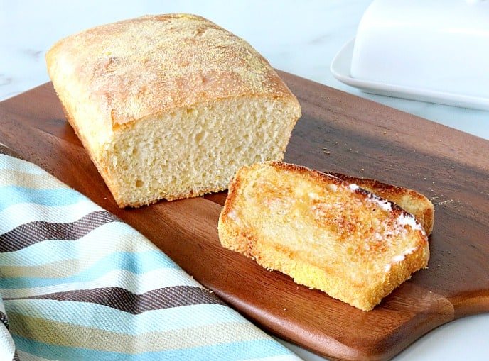 A loaf of English muffin bread on a dark brown cutting board with a blue and brown striped napkin.