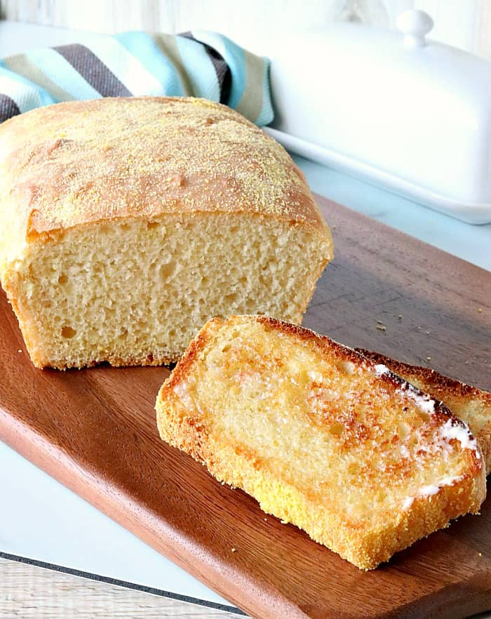 A vertical photo of a sliced loaf of English muffin bread with two toasted slices.