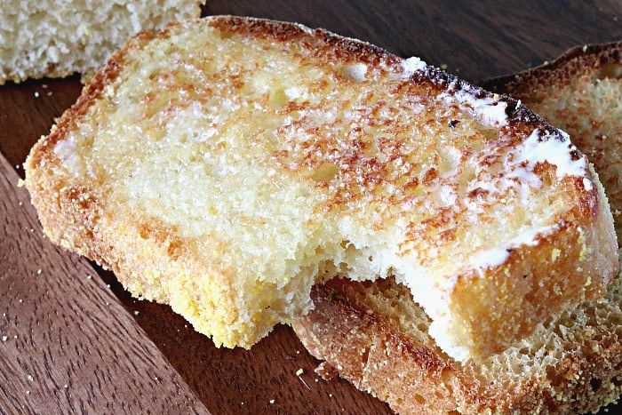A toasted slice of homemade English muffin bread with butter and a bite taken out.