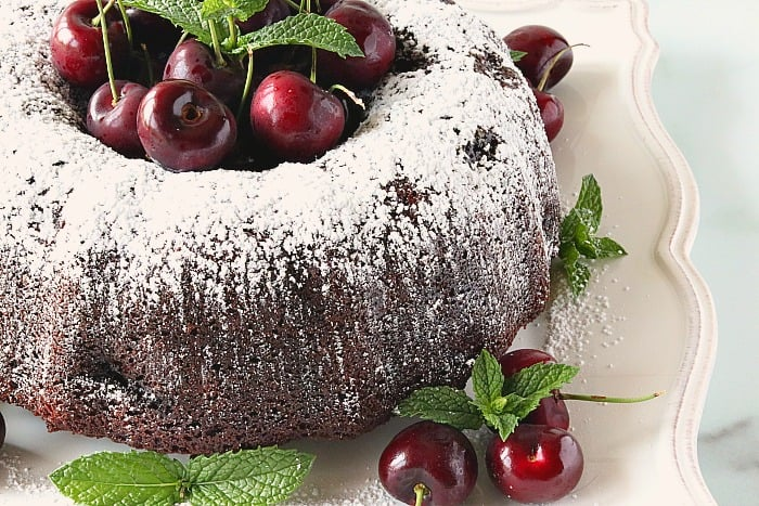 Closeup photo of a chocolate cherry bundt cake with a confectioners sugar dusting, fresh cherries, and mint.