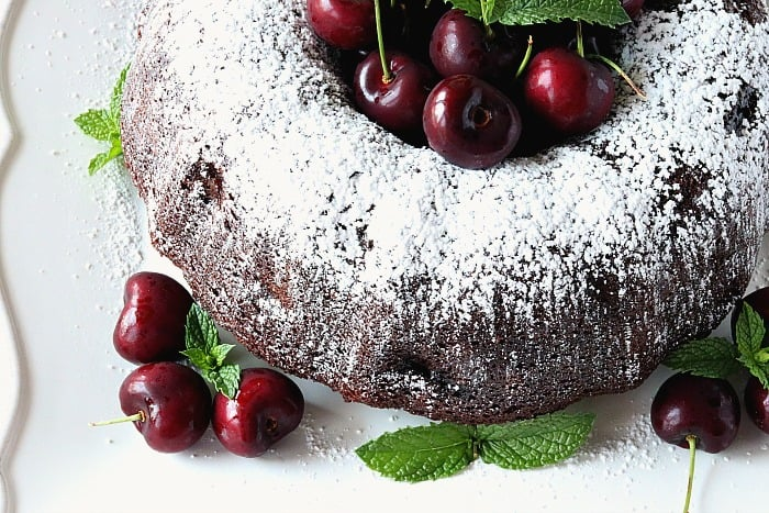 A closeup overhead shot of a chocolate cherry bundt cake with fresh cherries and mint.