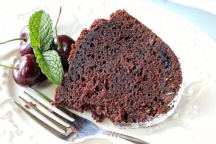 A slice of chocolate cherry bundt cake on a white plate with a fork, cherries, and mint.