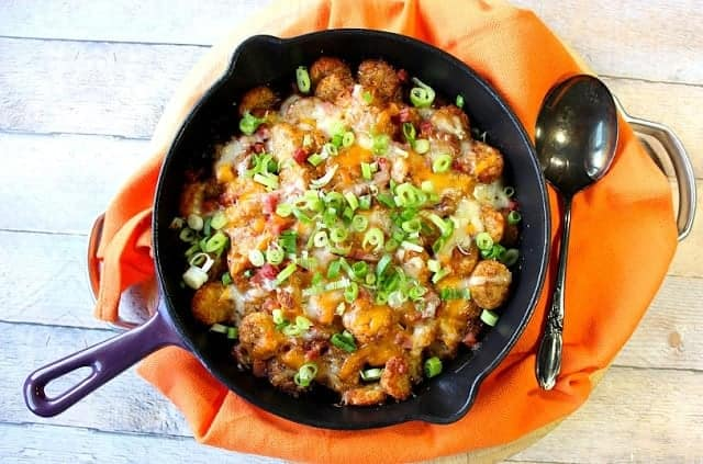 Overhead photo of a purple skillet filled with cheesy tater tot poutine with an orange napkin and a large spoon.