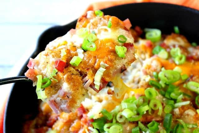 A closeup of a spoonful of tater tot poutine with cheese and green onion.