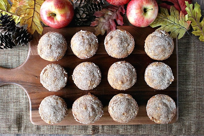 Overhead photo of a dozen apple cider donut muffins on a wooden board with apples, acorns and autumn leaves.