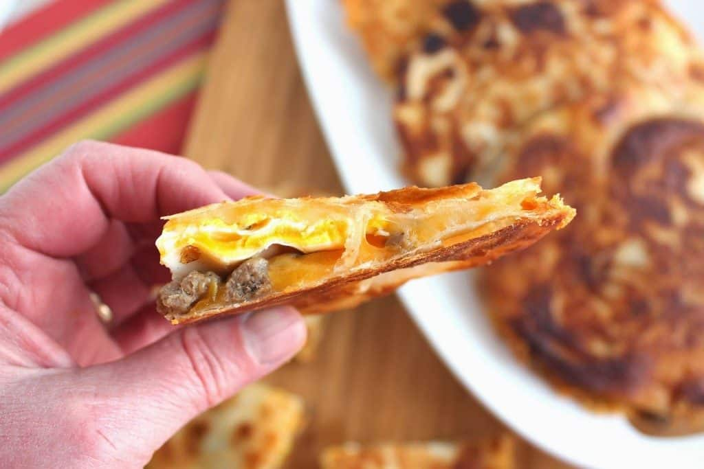 Closeup of the inside of a breakfast quesadilla with a fried egg, sausage, and cheese.