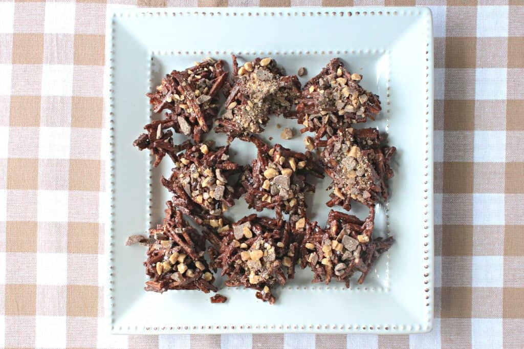 Overhead horizontal photo of a square white plate filled with chocolate covered shoestring haystacks with toffee bits.