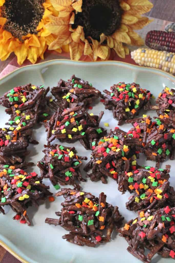 Closeup photo of a plate of chocolate covered shoestring haystacks with autumn sprinkles.