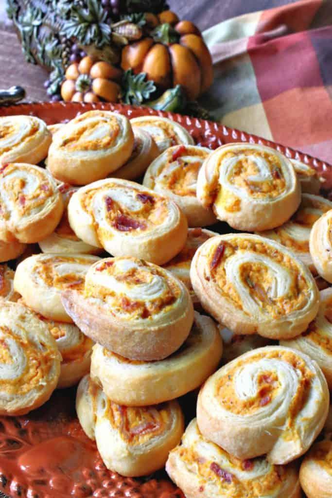 A orange platter piled high with pumpkin crescent pinwheel appetizers.