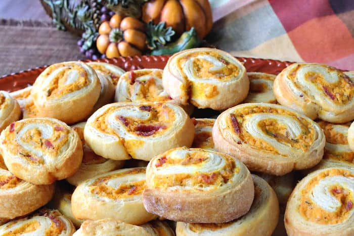 Closeup of a plate of crescent roll pinwheel appetizers filled with pumpkin, sage, and bacon.