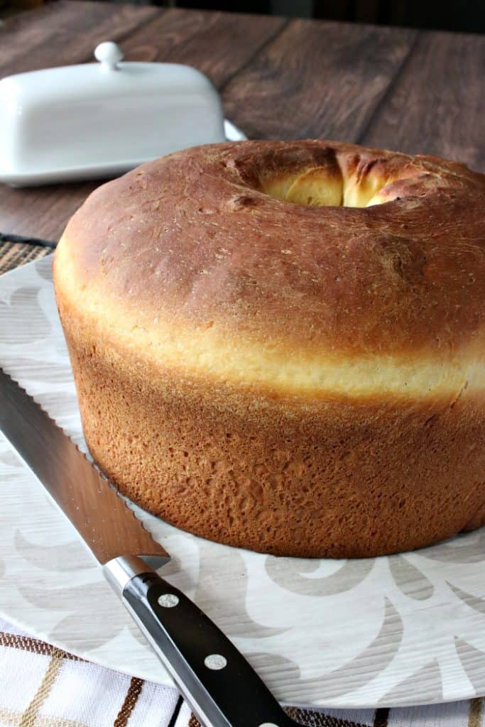 Vertical closeup image of an entire loaf of Sally Lunn batter bread on a plate with a serrated knife.