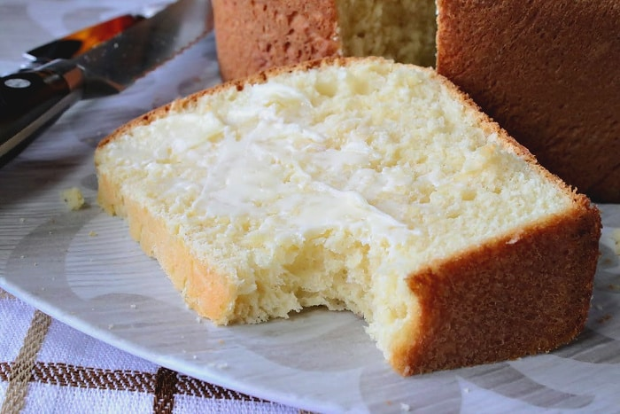 A closeup slice of a enriched batter bread with butter and bite taken out.