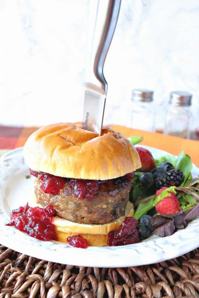 A vertical photo of a turkey burger with cranberry topping on a bun with a knife sticking into it.